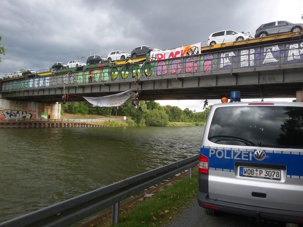 Aktivist*innen seilen sich von der Brücke ab, ihr Transparent ist nicht lesbar.