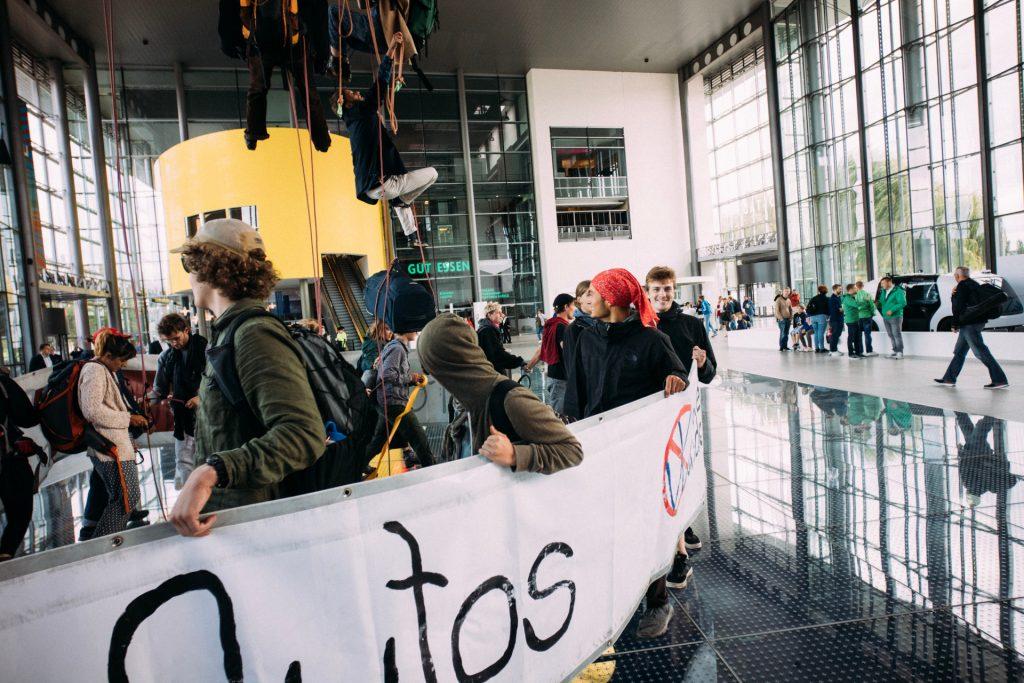 Aktivist*innen klettern zum Globus hoch, Demonstrant*innen schirmen sie ab.