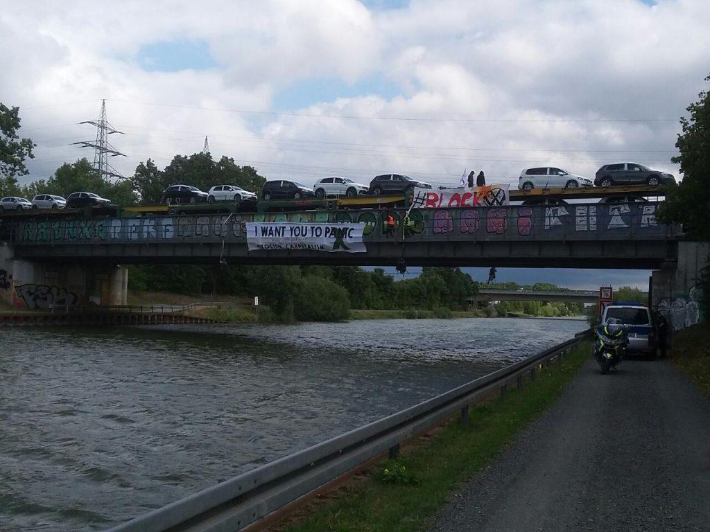 """Aktivist*innen hängen von der Brücke herunter - auf ihrem Transpi steht """"I want you to panic - abolish capitalism""""."""