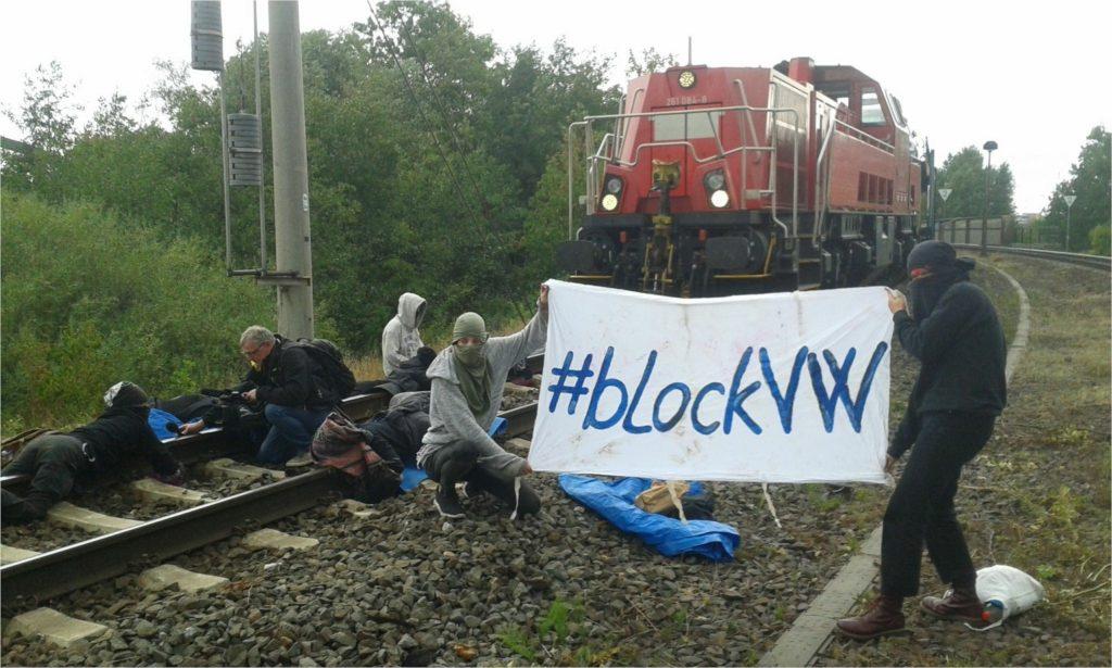 Aktivist*innen, die vor einem blockierten Zug angekettet sind. Auf ihrem Transpi steht #blockVW.