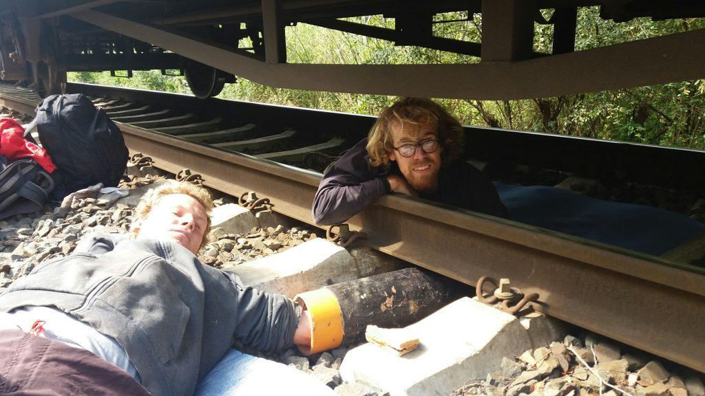 Zwei weitere Aktivist*innen haben sich unter einem Waggon angekettet und lächeln in die Kamera.