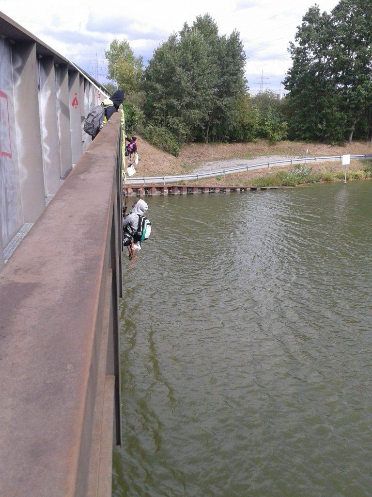 Menschen klettern an der Seite der Brücke herum.