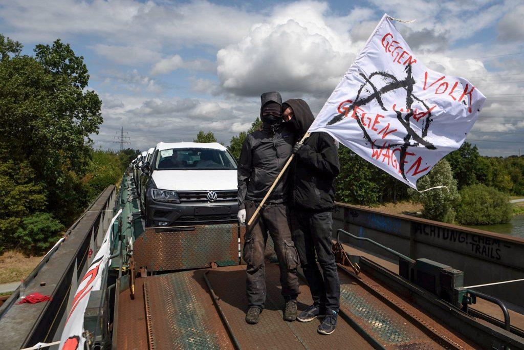 """Zwei Aktivistis stehen auf dem Autozug. Auf ihrer Fahne steht """"Gegen Volk und gegen Wagen""""."""